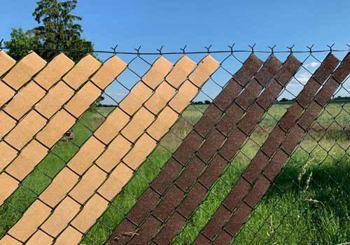 Detail stínění plotu. Textilie je propletena mezi oky plotu.